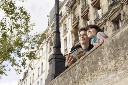 guidebook: France Paris Couple looking over bridge with guidebook