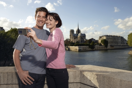 weekend break: Paris France Couple taking a photo of themselves in front of Notre Dame Cathedral