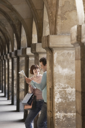 weekend break: Couple with shopping bags looking at map under archway LANG_EVOIMAGES