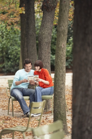 weekend break: Couple reading guide book sitting on chairs in park
