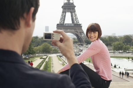 two people with others: Couple Using Camera Phone and Eiffel Tower LANG_EVOIMAGES