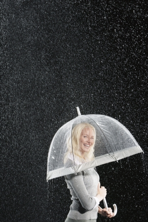 Smiling businesswoman Standing Under Umbrella during rain Stock Photo - 18897272