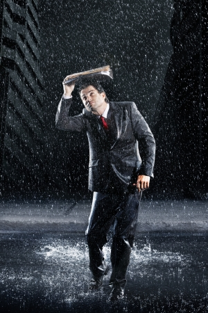 drenched: Businessman covering head with binder running through rain LANG_EVOIMAGES