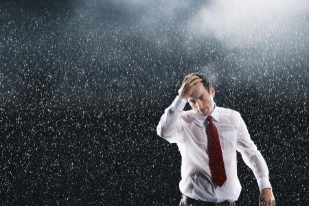 uomo sotto la pioggia: Imprenditore in esecuzione mani tra i capelli bagnati in piedi sotto la pioggia LANG_EVOIMAGES