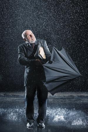 UOMO pioggia: Uomo d'affari che lotta per aprire l'ombrello durante pioggia improvvisa