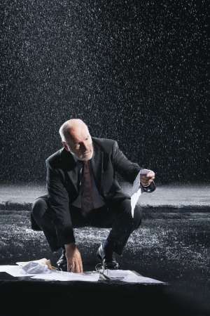downpour: Businessman Picking up soaked Paperwork during downpour