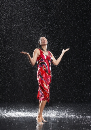 downpour: Woman arms raised smiling standing in rain LANG_EVOIMAGES