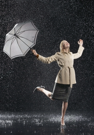 wide wet: Woman standing on one leg holding umbrella leaning into falling rain