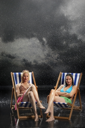 downpour: Sunbathers sitting in sunloungers during downpour