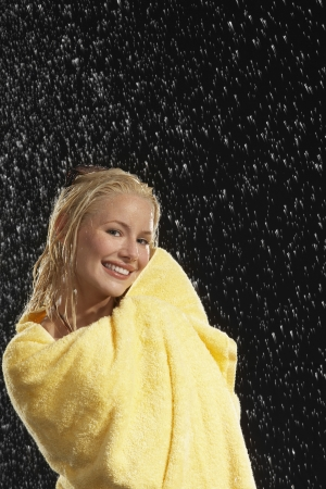 hair wrapped up: Smiling Woman Wrapped in Towel Standing in Rain LANG_EVOIMAGES