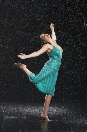 wide  wet: Woman standing on one leg leaning into falling rain