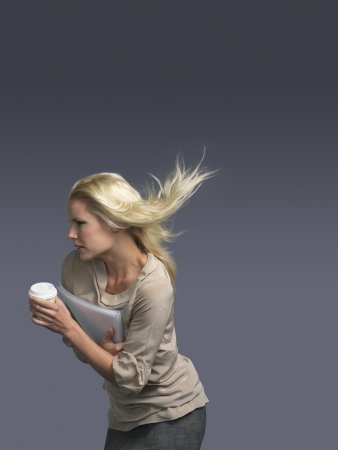 blowing wind: Woman with hair blowing holding coffee facing into wind