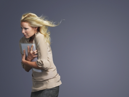 blonde hair: Woman with hair blowing facing into wind side view