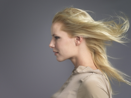 blowing of the wind: Woman Facing the Wind hair billowing behind profile close-up
