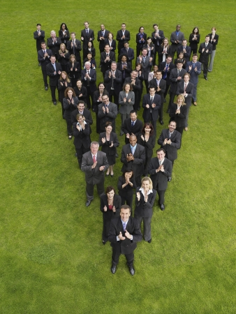 large formation: Large group of business people standing in triangle formation, clapping, elevated view