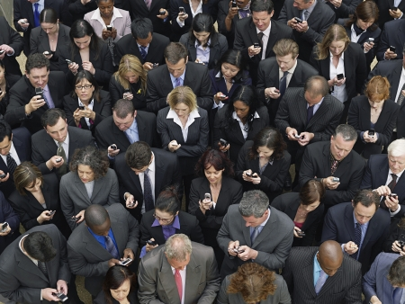 business man phone: Large group of business people text messaging elevated view