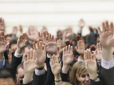 mixed age range: Multitud de personas que levantan las manos centran en las manos