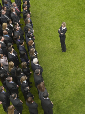 large formation: Business woman facing large group of business people in formation, elevated view LANG_EVOIMAGES