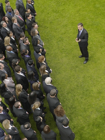 mixed age range: Business man facing large group of business people in formation, elevated view LANG_EVOIMAGES