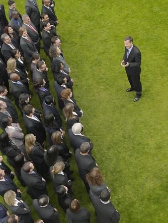 mixed age range: Hombre de negocios que enfrenta gran grupo de personas de negocios en la formaci�n, visi�n elevada