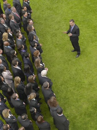 Business man facing large group of business people in formation, elevated view Stock Photo