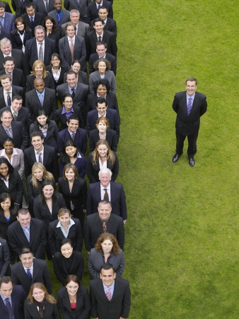 large formation: Business man standing next to large group of business people in formation, elevated view, portrait