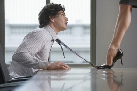 dominare: Imprenditrice in piedi sulla scrivania pestare cravatta vista laterale di uomo d'affari