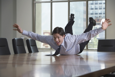 out of business: Businessman sliding on stomach on conference room table