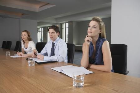 receptivo: Tres empresarios que se sientan en mesa de conferencias