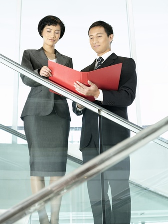 reviewing documents: Business colleagues reviewing documents while standing on stairs
