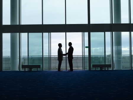 clandestine: Businessmen Shaking Hands in doorway silhouette profile