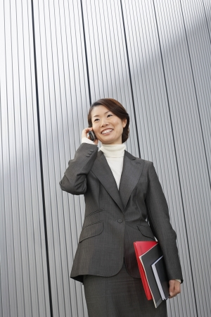 Businesswoman holding paperwork using Cell Phone Stock Photo - 18897468