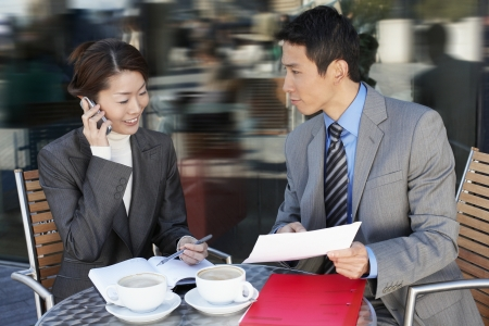 reviewing documents: Businesspeople Meeting at outdoor Cafe talking on phone reviewing documents
