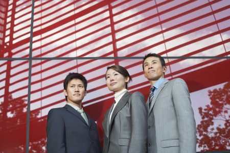 Businesspeople Standing outside beside red Building low angle view Stock Photo - 18897510