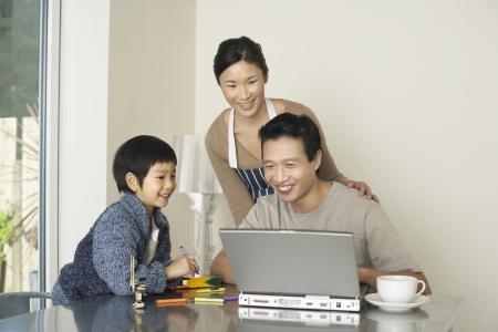 Father working on computer at dining room table wife and son watching Stock Photo - 18897525