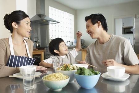 familia comiendo: Familia joven que se sienta en la mesa de la cocina interacci�n antes de la comida LANG_EVOIMAGES