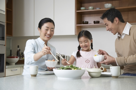 family one: Coppia giovane e la figlia a mangiare un pasto con le bacchette sul bancone della cucina