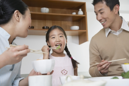 asian bowl: Young couple and daughter eating a meal with chopsticks LANG_EVOIMAGES