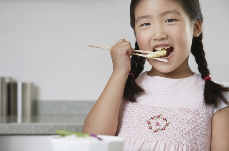 baby corn: Young Girl with pigtails Eating Baby Corn with chopsticks