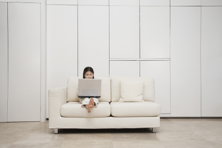 Young barefoot Girl Using Laptop on Sofa Stock Photo - 18897556
