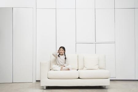 Young barefoot Girl sitting cross-legged Sofa Stock Photo - 18897557