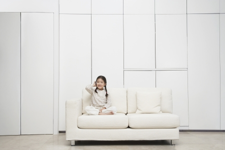 Young barefoot Girl sitting cross-legged Sofa Stock Photo - 18897557