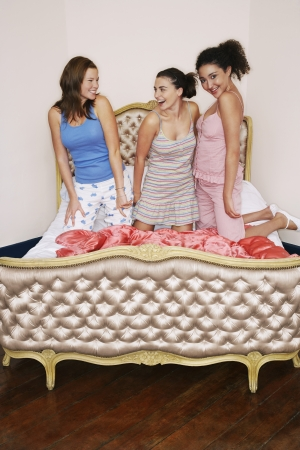 soir�e pyjama: Jeunes filles au Slumber Party genoux sur un lit g�nial LANG_EVOIMAGES