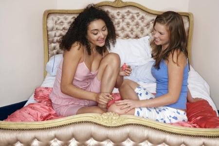 soir�e pyjama: Les ongles de peinture adolescente ami sur le lit � la soir�e pyjamas