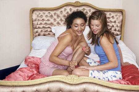 slumber: Teenage girl painting friends fingernails on bed at slumber party