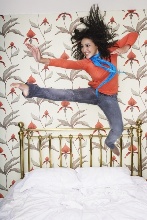 long weekend: Teenage Girl arms outspread kicking jumping on bed
