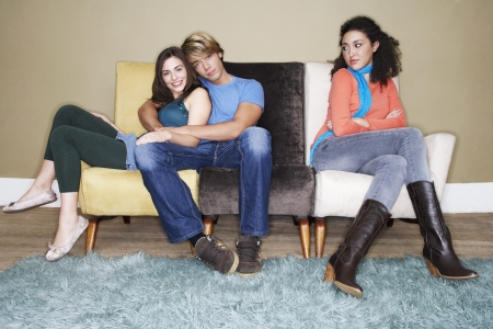 third wheel: Third wheel sitting arms crossed on opposite end of sofa of hugging couple LANG_EVOIMAGES
