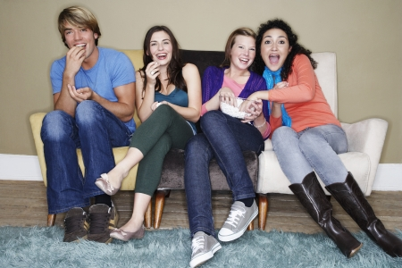 watching movie: Friends sitting eating popcorn watching movie on sofa LANG_EVOIMAGES