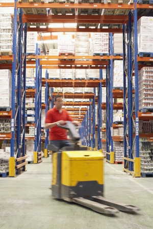 Mid-adult Man Driving Pallet Jack Through Warehouse Stock Photo - 18897627