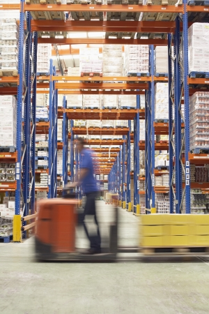warehouse worker: Mid-adult Man Driving Pallet Jack Through Warehouse side view